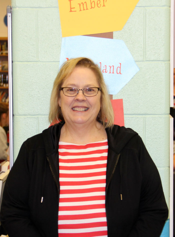 Mrs. Dana Wright standing in front of her library sign.