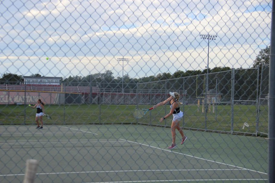 Grove+stands+behind+the+line+as+she+serves+the+ball+over+the+net.+