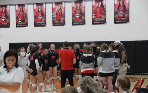 The volleyball team gathers in a timeout during their game against Kenton Ridge.