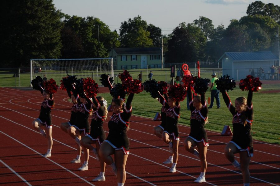 The cheerleaders performing a cheer for crowd before the game starts.