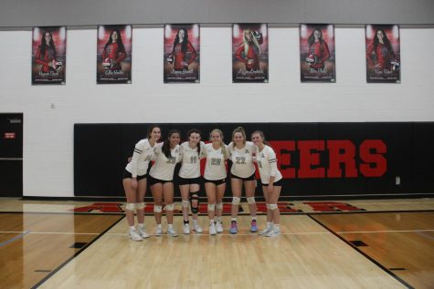 Seniors pose for a picture under their banners